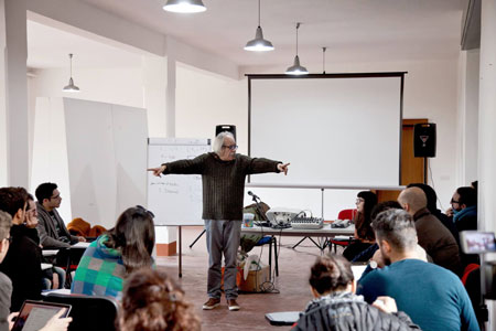 Foto scattata durante corso del Cineporto: un docente spiega a diversi ragazzi.