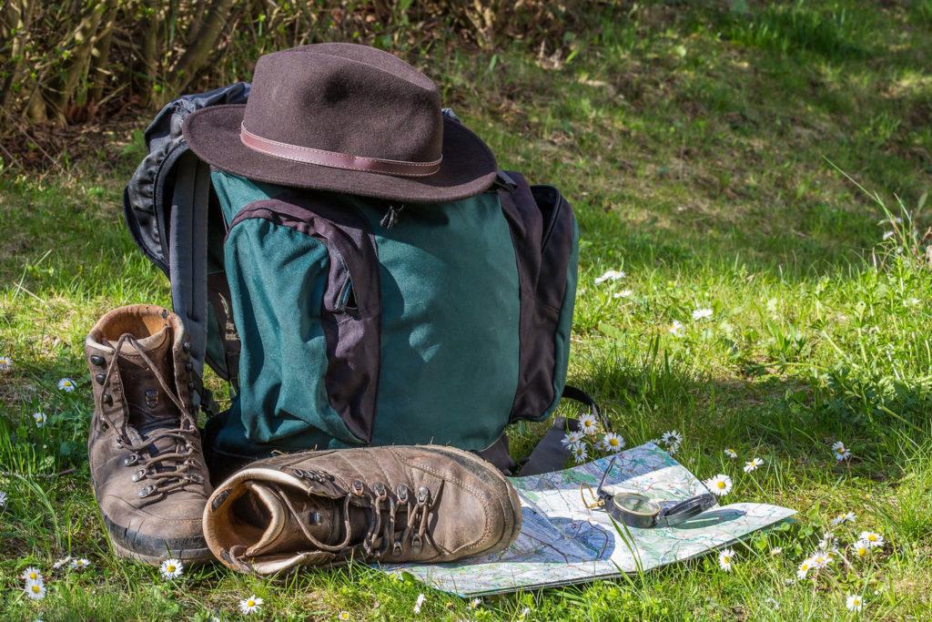 Zainetto, mappa, cappello e scarpe da trekking.