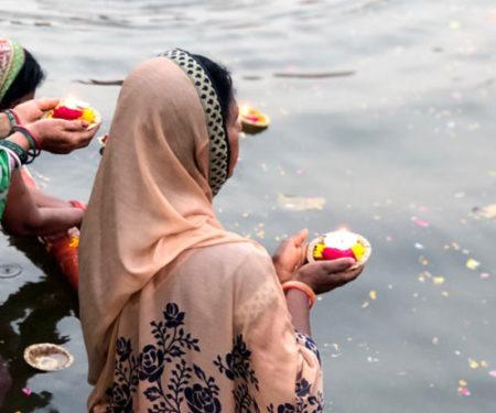 Foto di una donna con vestito tradizionale che sull'acqua compie un rituale con una candela.